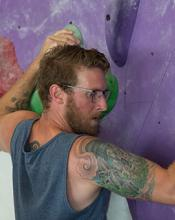 Scott Christenson climbing an indoor climbing wall